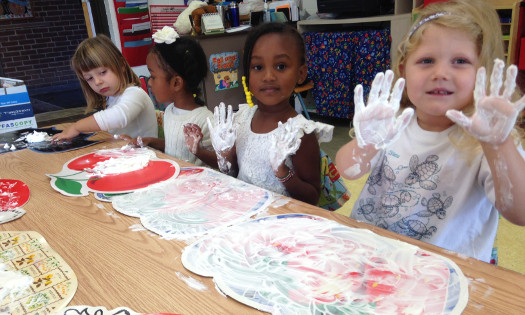 nursery school students sitting at a table and fingerpainting