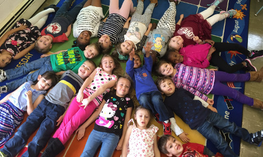 nursery school students lying in a circle on the floor